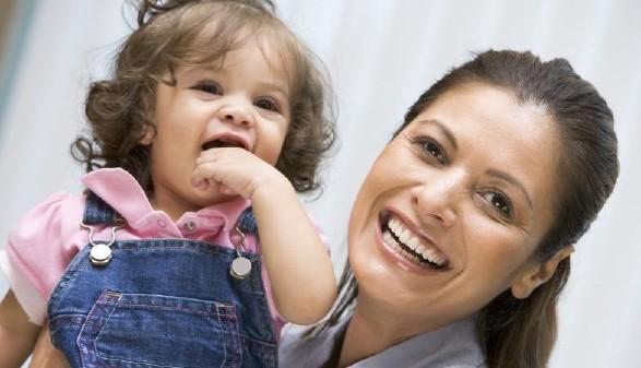 Frau hält Kind und lächelt © Monkey Business, stock.adobe.com