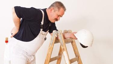 Maler mit Rückenschmerzen steht neben einer Leiter © Cello Armstrong, stock.adobe.com