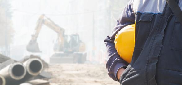 Bauarbeiter-Helm wird in der Hand gehalten, im Hintergrund eine Baustelle © astrosystem, stock.adobe.com