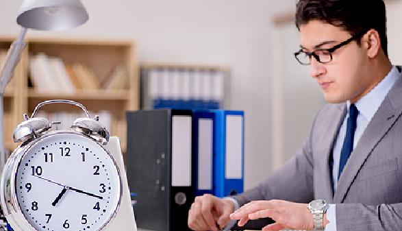 Büroangestellter mit Brille sitzt vor Laptop und Uhr © Elnur, Fotolia.com