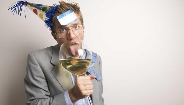 Mann mit Partyhut und großem Weinglas. © PeskyMonkey, Adobe Stock