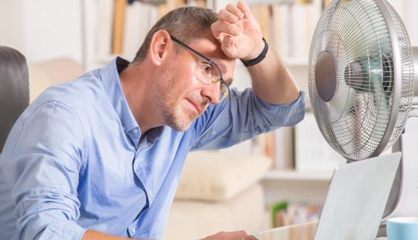 Arbeiten bei Hitze, man sitzt im Büro vor Ventilator und schwitzt © Monika Wisniewska, stock.adobe.com