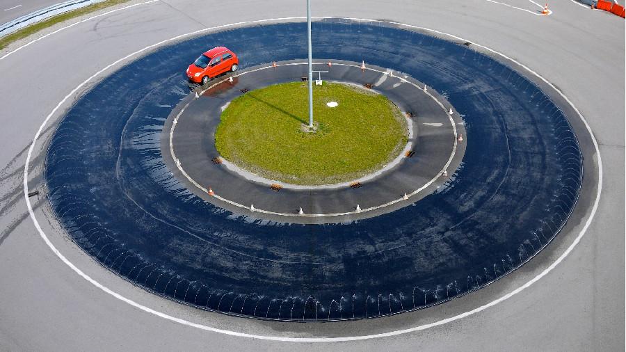 Auto fährt im Kreisverkehr bei nasser Fahrbahn. © ARBÖ, ARBÖ zVg.