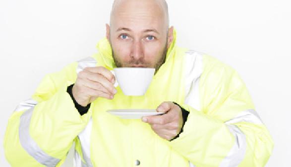 Ein Mann in Arbeitskleidung nippt an einer Tasse Tee, in der anderen Hand hält er die Untertasse. © stock.adobe.com