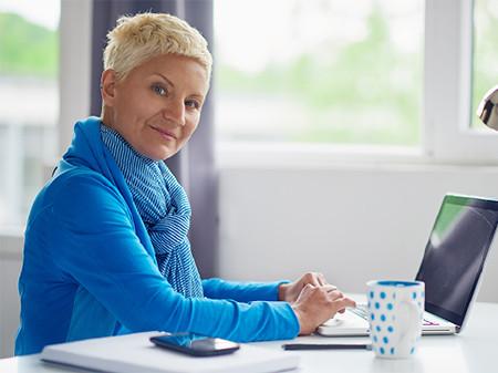 Angestellte sitzt bei der Arbeit am Laptop und schaut in die Kamera © chika_milan, Fotolia.com