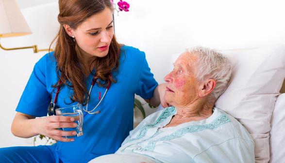 Frau betreut ältere Dame am Bett © Sandor Kacso, stock.adobe.com