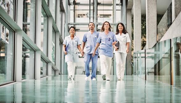 Pflegepersonal marschiert einen langen Gang entlang © Robert Staudinger, TBWA