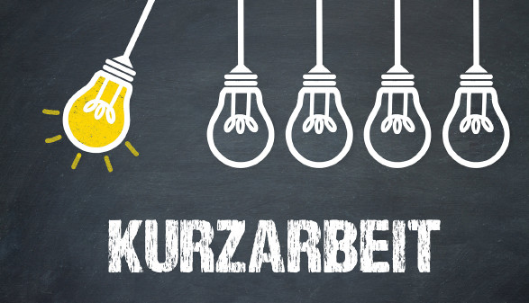 Fünf Glühbirnen hängen über dem Schriftzug Kurzarbeit, eine davon schwingt und leuchtet © magele-picture, stock.adobe.com