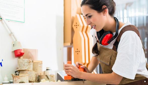 Weiblicher Tischlerlehrling beim Hobeln eines Holzstückes © Kzenon, Fotolia.com