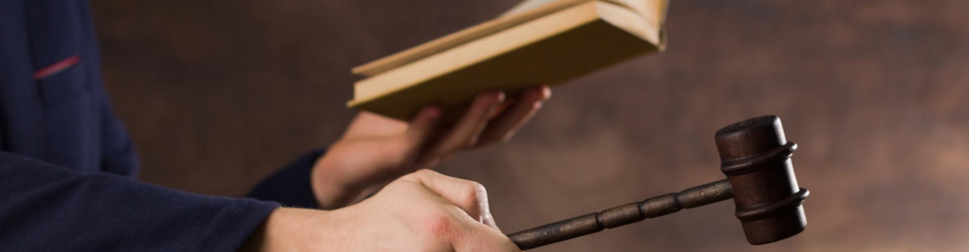 Man sieht zwei Hände. Eine hält ein Gesetzbuch, die andere einen Hammer © Chodyra Mike, stock.adobe.com