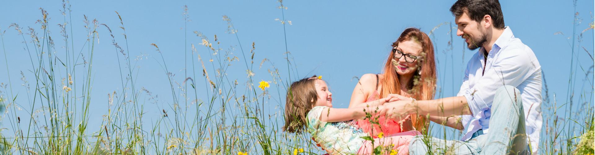 Eltern mit Tochter auf Wiese © Minerva Studio , adobe.stock.com
