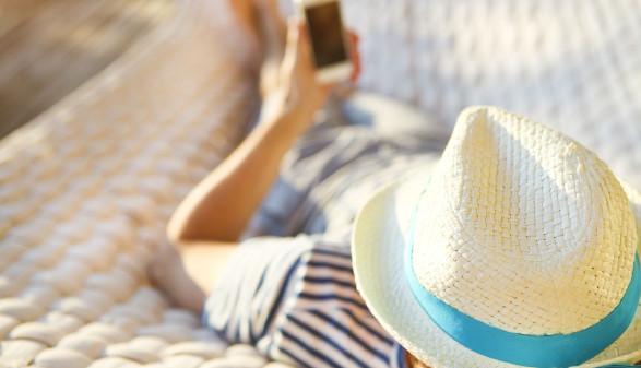 Mann liegt in einer Hängematte, hat einen Hut auf und hält Handy in seiner Hand © Dasha Petrenko, stock.adobe.com