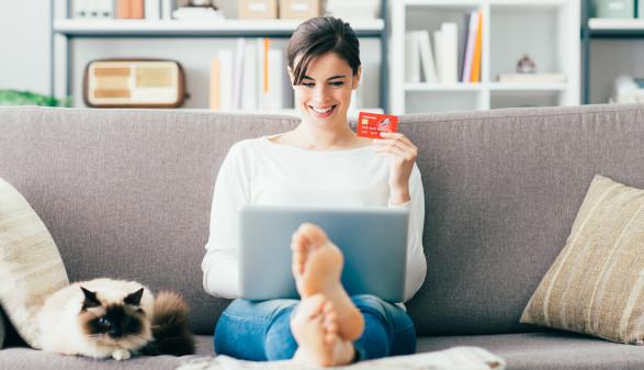 Frau sitzt am Sofa und kauft online etwas ein © stokkete, stock.adobe.com
