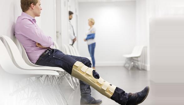 Junger Mann sitzt mit geschientem Bein im Wartezimmer © biker3 , Arbeiterkammer Oberösterreich