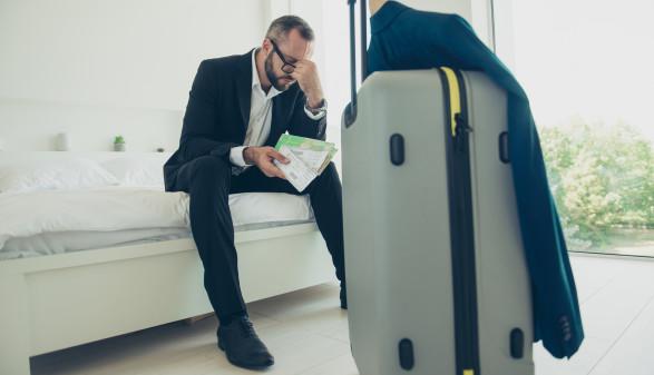 Man sitzt genervt auf dem Bett, vor ihm sein Reisekoffer. © deagreez, stock.adobe.com