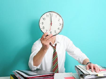 Mann sitzt am Schreibtisch und hält sich eine Wanduhr vors Gesicht © granata68, stock.adobe.com