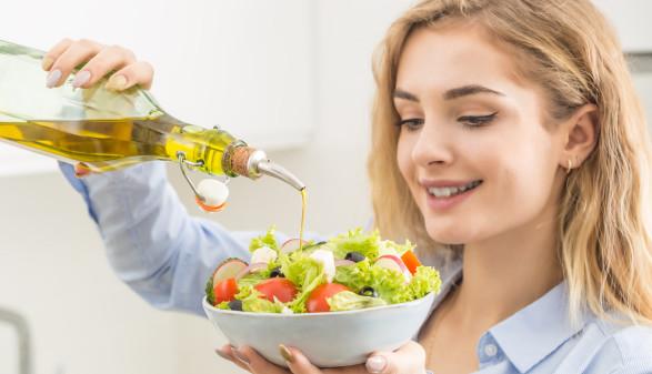 Frau leert Olivenöl über Salat © weyo, stock.adobe.com