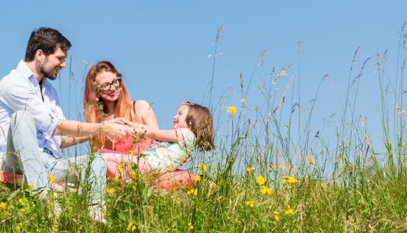 Familie hält sich an den Händen im Sommer, sie sitzen auf einer Blumenwiese ©  Kzenon, stock.adobe.com