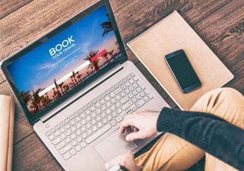 Mann sitzt vor Laptop und bucht eine Online-Reise © customdesigner, stock.adobe.com