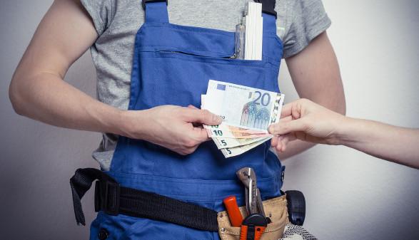 Bauhandwerker bekommt Geldscheine © DDRockstar, stock.adobe.com