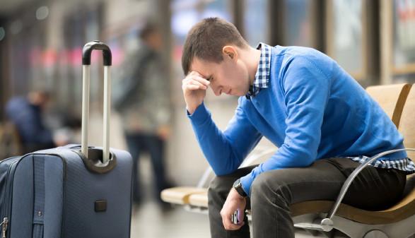 Urlauber sitzt mit Koffer nachdenklich am Flughafen © fizkes, Fotolia.com