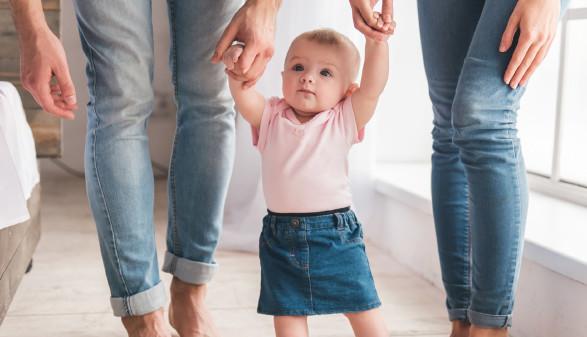 Kleinkind lernt gehen und wird dabei von Mutter und Vater an den Händen gehalten © georgerudy, Fotolia.com
