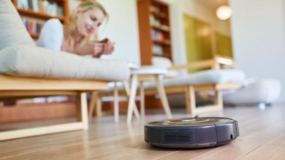 Saugroboter saugt das Wohnzimmer mit Frau im Hintergrund © Robert Kneschke, stock.adobe.com