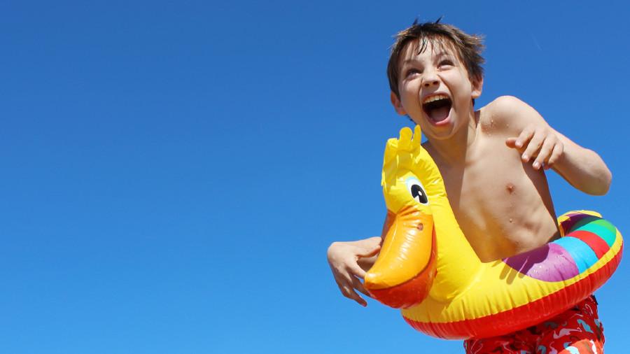 Lachender Bub am Meer mit Schwimmreifen © Natallia Vintsik , Adobe Stock