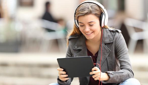 Frau sieht auf Tablet und benützt ein HeadSet © Antonio Guillem, stock.adobe.com